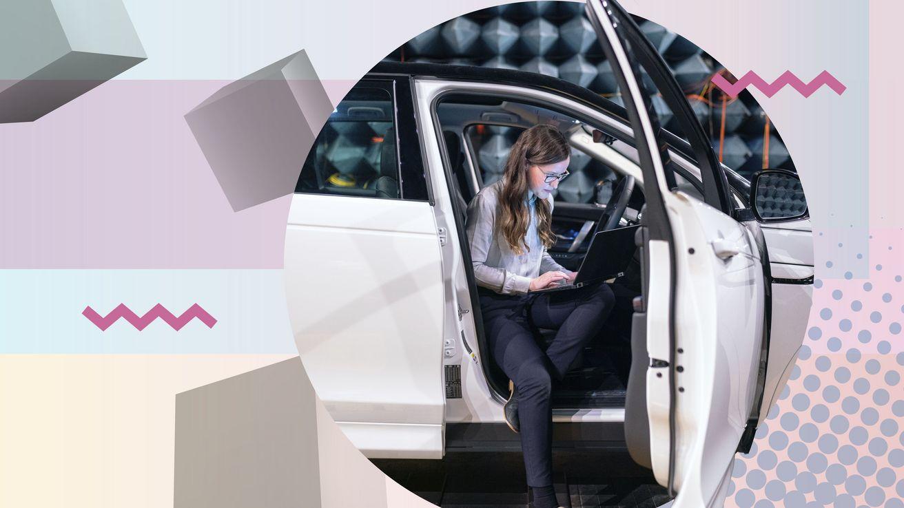 Eine Frau sitzt in der geöffneten Tür eines Autos und arbeitet an einem Laptop.